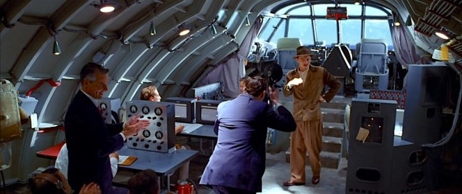 """Hughes in the fuselage of the Hercules before its historic maiden flight, decked out in shades of brown from head to toe, presenting a surprisingly grounded sartorial approach for a man hoping to get his """"Spruce Goose"""" into the air. Though Glenn Odekirk is shown in the scene (as Matt Ross' head can be seen here), Odie was not actually on the famous flight as Hughes wanted to remove any doubt that anyone but he was at the controls."""