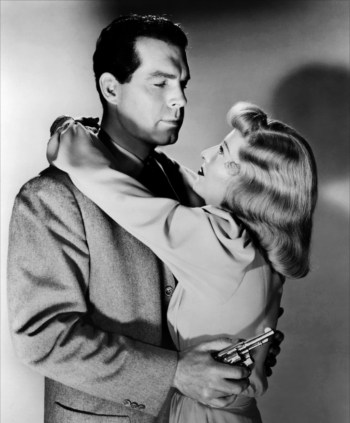 Studio portrait of Fred MacMurray and Barbara Stanwyck—with her prop Smith & Wesson .32—in Double Indemnity (1944)