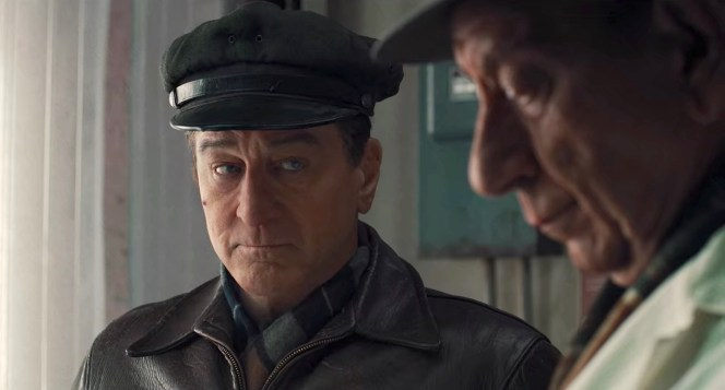Frank warily eyes his boss from under the brim of his peaked cap.