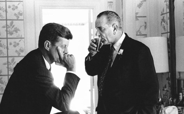 LBJ enjoys what's likely one of his usual Scotch highballs with JFK.