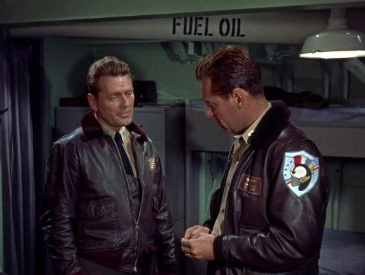 CDR Wayne Lee (Charles McGraw) joins LT Brubaker in his own flight jacket with a mouton fur collar, though Lee only wears the Carrier Air Group 19 patch (as seen here on Brubaker's left sleeve).