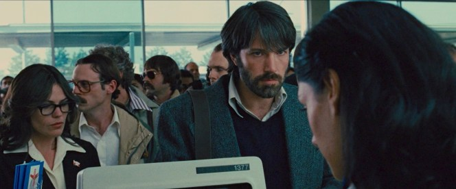 Tony and the six diplomats try to conceal their anxiety as the ticket agent encounters trouble finding their flight reservations.