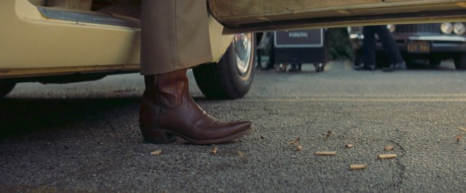Rick steps out of his Caddy, pounding his discarded cigarette butts with his cowboy boots.