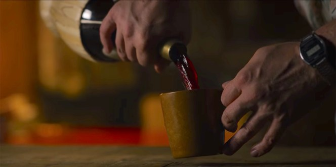 Hop pours himself a mug full of Chianti when he gets home from his jilted date with Joyce.