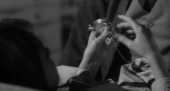Scout admires her father's timepiece. (In this earlier scene, he's wearing his cardigan over the waistcoat and trousers of his light worsted suit.)