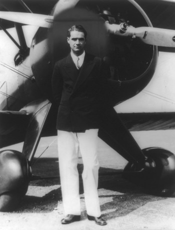 The real Howard Hughes, dressed similarly to DiCaprio's depiction, standing in front of his new Boeing 100A Army Pursuit Plane in Inglewood, California, during the 1940s.