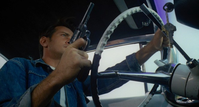 Driving with his finger on the trigger is consistent with Kit's reckless personality.