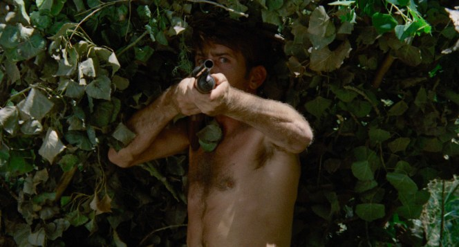 Slowly emerging from the ground like Captain Willard from the swamp, Kit guns down three bounty hunters with his Remington Model 870.