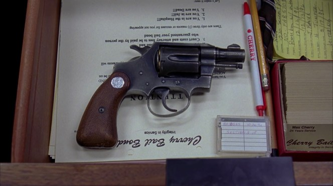 Max Cherry's desk, complete with letterhead forms, branded ballpoint pen, and a loaded .38 snub. The Colt can be identified as a second generation Detective Special by the half-ramped front sight, long (non-shrouded) ejector rod with its grooved knurled tip, and the lack of a locking pin next to the frame screw between the cylinder and the trigger.