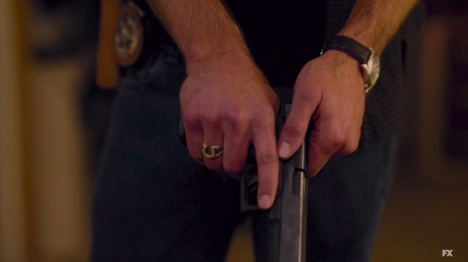 Raylan ejects a round from his Glock.