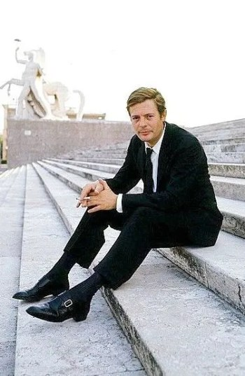 Marcello Mastroianni in color, sporting the black suit, tie, and monk shoes that may have been the same costume from La Dolce Vita.