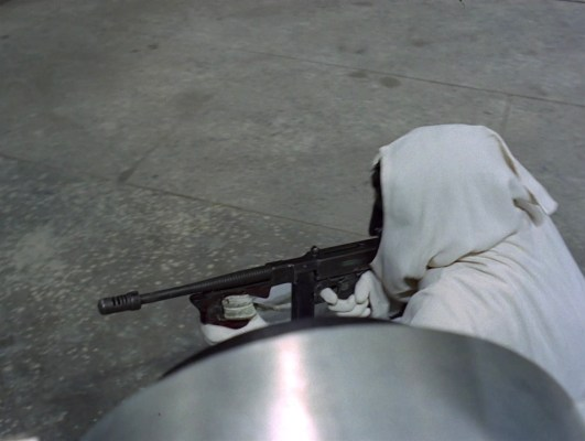 """A hooded Number 6 takes cover and takes aim with his Tommy gun in """"Fall Out""""."""