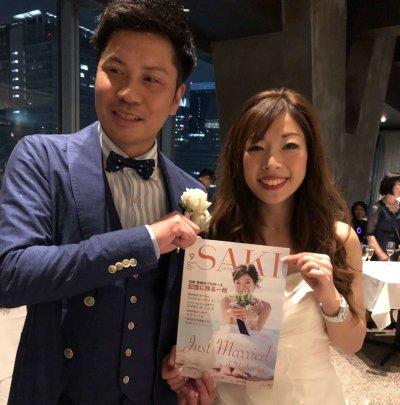 結婚式の二次会にて撮影された写真。新郎新婦も新聞の出来ににっこり