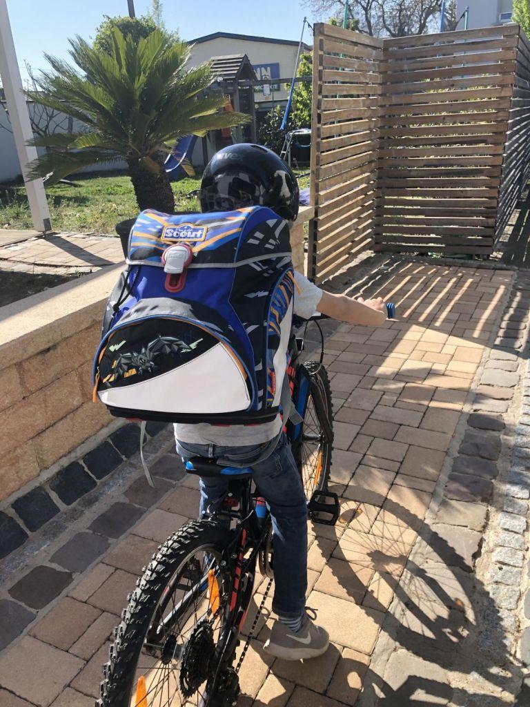 Big D auf dem Fahrrad mit dem SCOUT ALPHA Schulranzen von rechts