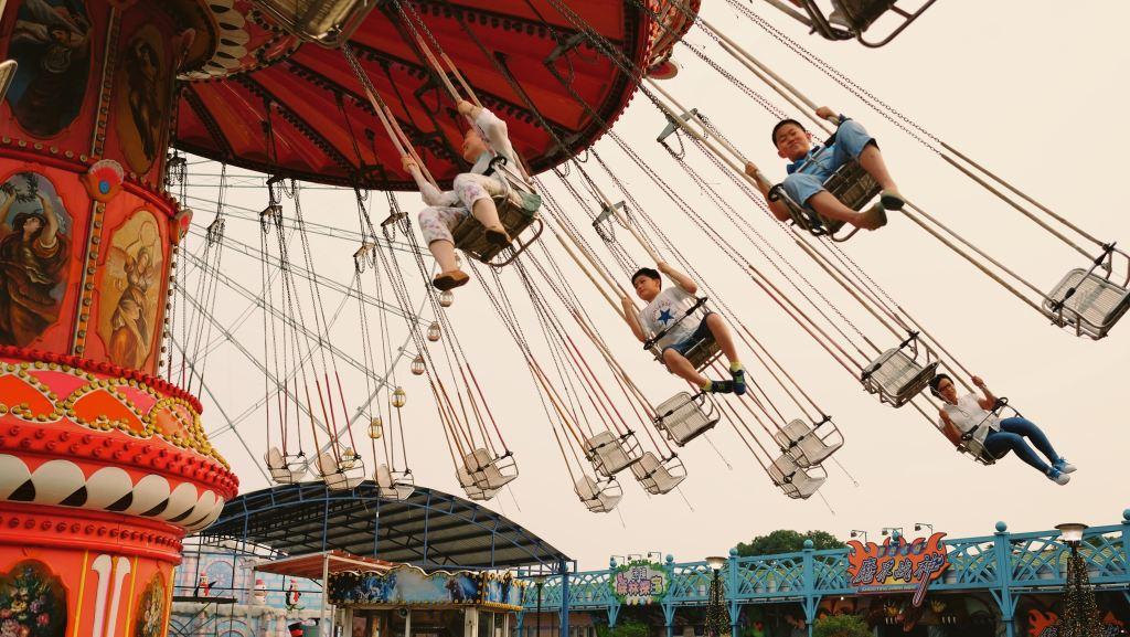 a photo of carnival people on swings