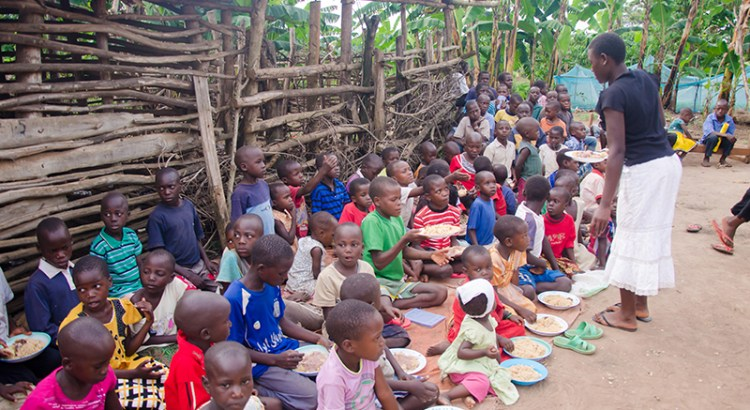 Children sited in the dusty compound having a meal
