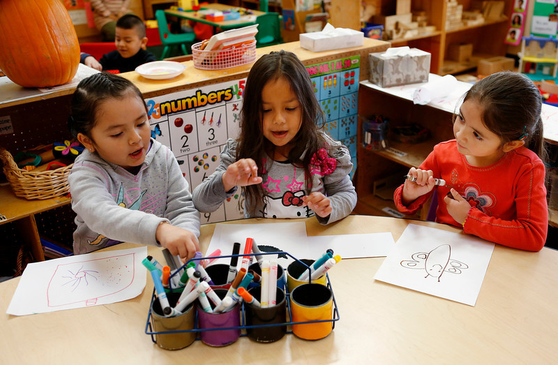 Amairany Lopez, 4, Marydel Duldulao, 4, and Kaylee Barragan, 4, enjoy drawing together during free time at St. Elizabeth's Day Home in San Jose, Calif., on Wednesday, Feb. 19, 2014. Democrats propose to expand the state's transitional kindergarten program for four-year-olds. St. Elizabeth's Day Home is one of San Jose's oldest preschools and could provide a model for the state. At left rear is Jose Orozco, 4. (Gary Reyes/Bay Area News Group)
