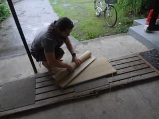 Hendrik Lindelauf preparing tatami mats for cut (curling, water etc)