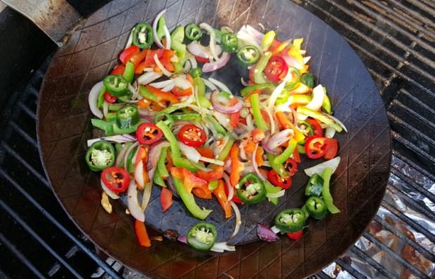 Paprika, Zwiebeln und Jalapenos werden in der Eisenpfanne angebraten