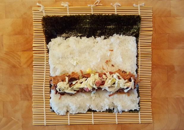 Pulled Pork, BBQ Sauce und Coleslaw auf den Reis geben