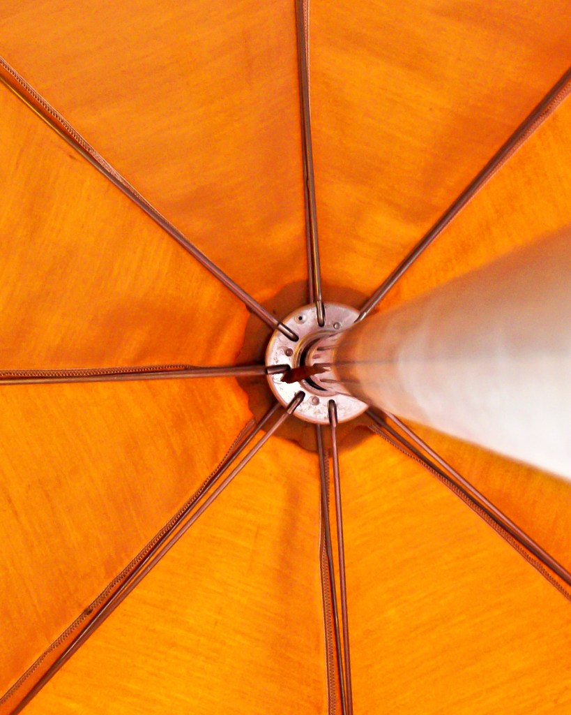 Artistic view of metal workings under a bright orange umbrella