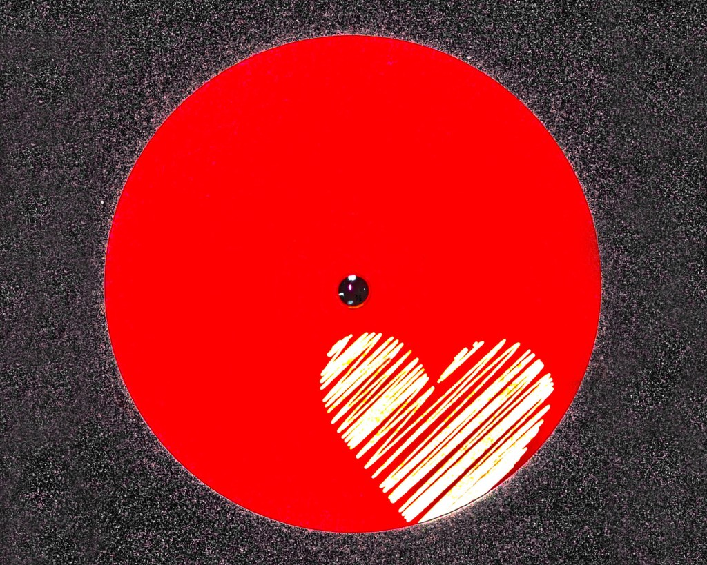 Red circle with white scribble heart from center label of vinyl record