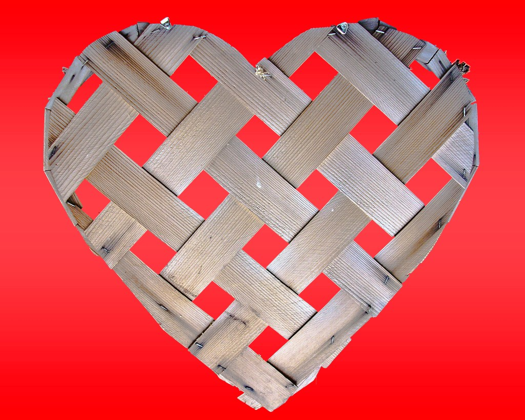Wooden checkered heart nailed onto a blood red background representing love