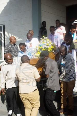 Pallbearers escorting the casket to the gravesite.