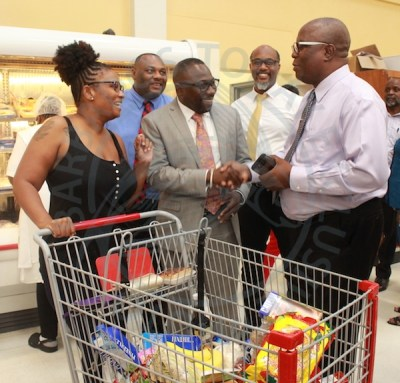 Minister of Commerce Dwight Sutherland greets managing Director of Popular Discount Bertram Hall, as (from left) shopper Sherry-Ann Thorington, Permanent Secretary in Ministry of Commerce Terry Bascombe and acting Director in the Department of Commerce Bertram Johnson look on.