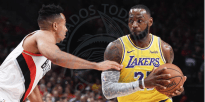 Lakers' LeBron James is guarded by Portland's CJ McCollum last night in their season opener.