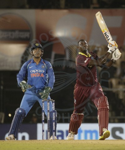 Captain Jason Holder and wicketkeeper MS Dhoni follow the direction of the ball as it goes for six. Holder's was the only bright performance for the Windies in today's fourth ODI.