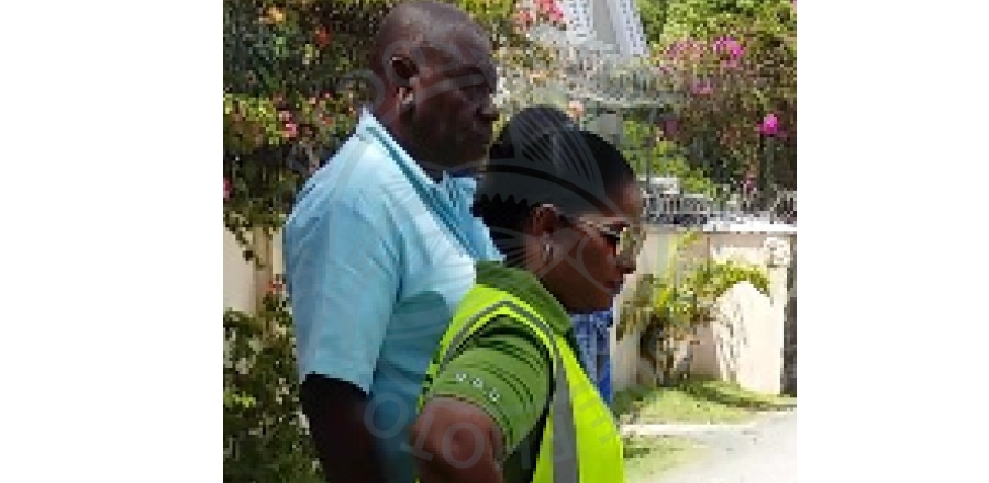 The BWA's Corporate Communications and Rapid Response Manager Joy-ann Haigh and Acting Senior Superintendent of Works Randy Phillips assess the water-logged trench at Rawlins Road, Brittons Hill this afternoon.