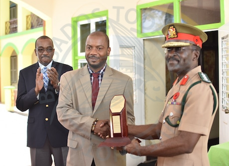Parliamentary Secretary in the Ministry of Elder Affairs Neil Rowe (centre) presents a token of appreciation to Barbados Defence Force Chief of Staff Colonel Glyne Grannum (right) for its contribution to the maintenance of the Geriatric Hospital.