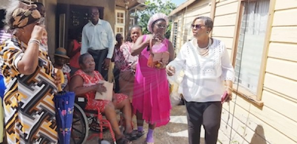 Member of Parliament for St Thomas Cynthia Forde (right) speaking to residents at Dunscombe, St Thomas where a tractor fell off a trailer and crashed into the living room of the home of two elderly women this morning. Sitting in the wheelchair is 76-year-old Lavadne Edwards-Harris who is one of the occupants of the house, which was damaged.