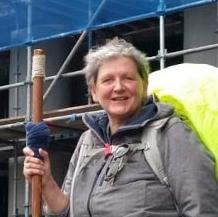 Barbara Jikai, hoofd en schouders, bij het startpunt van het Jabikspaad Grijze jas. Fel gele regenhoes over de rugzak. Houten pelgrimsstaf.