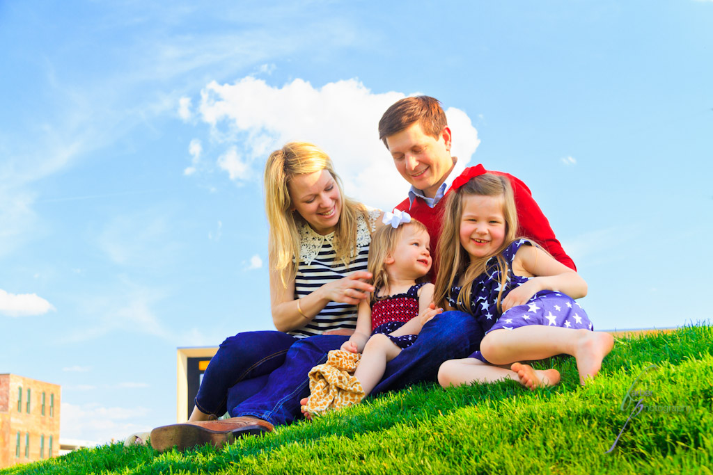 Family sitting on grassy hill with blue sky and clouds