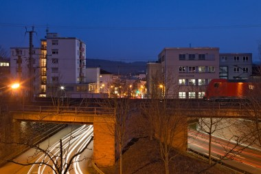 Kunstbauten von Verkehrsbändern sind die Stadtmauern der Neuzeit. Ihre durchgezogenen Horizonte und eingehaltenen Radien verlangen Brücken und Schneisen, die ihrerseits ungewollt und beiläufig räumliche Faltungen und Kammerungen erzeugen. Diese können dann von einer derartigen Zufälligkeit sein, dass sie unverwechselbar werden und als Besonderheit das Stadtbild schmücken. Nordweststadt – Emil-Strauß-Straße – März 2015