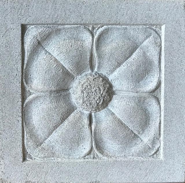 A shallow carving in limestone of a four petal flower.