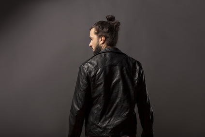 back view of man with beard and bun in black leather jacket