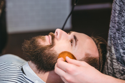 Cleaning clients face after haircut with soft brush in barber shop