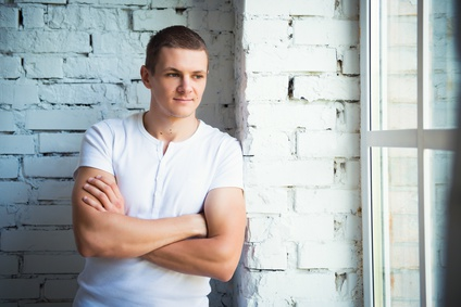 Young attractive man standing near the window and a white brick wall
