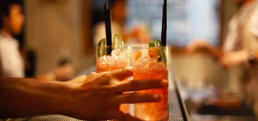 a hand holding to tumbler glasses full with a orangy cocktail on a bar counter