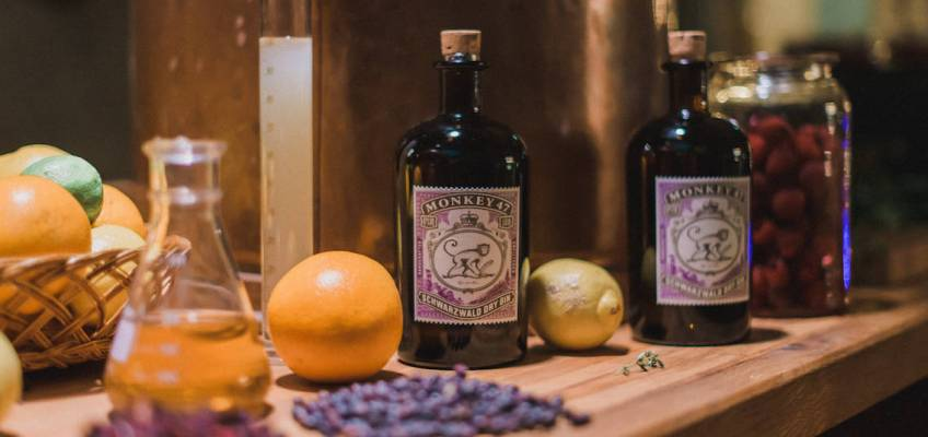 Monkey47 bottle on a wooden counter next to a lemon, orange a lavander flowers