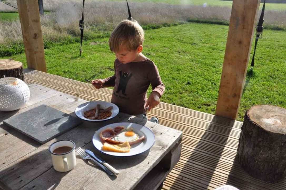 boy eating breakfast cooked on the stove in rusty the tin tent at barefoot glamping Cornwall