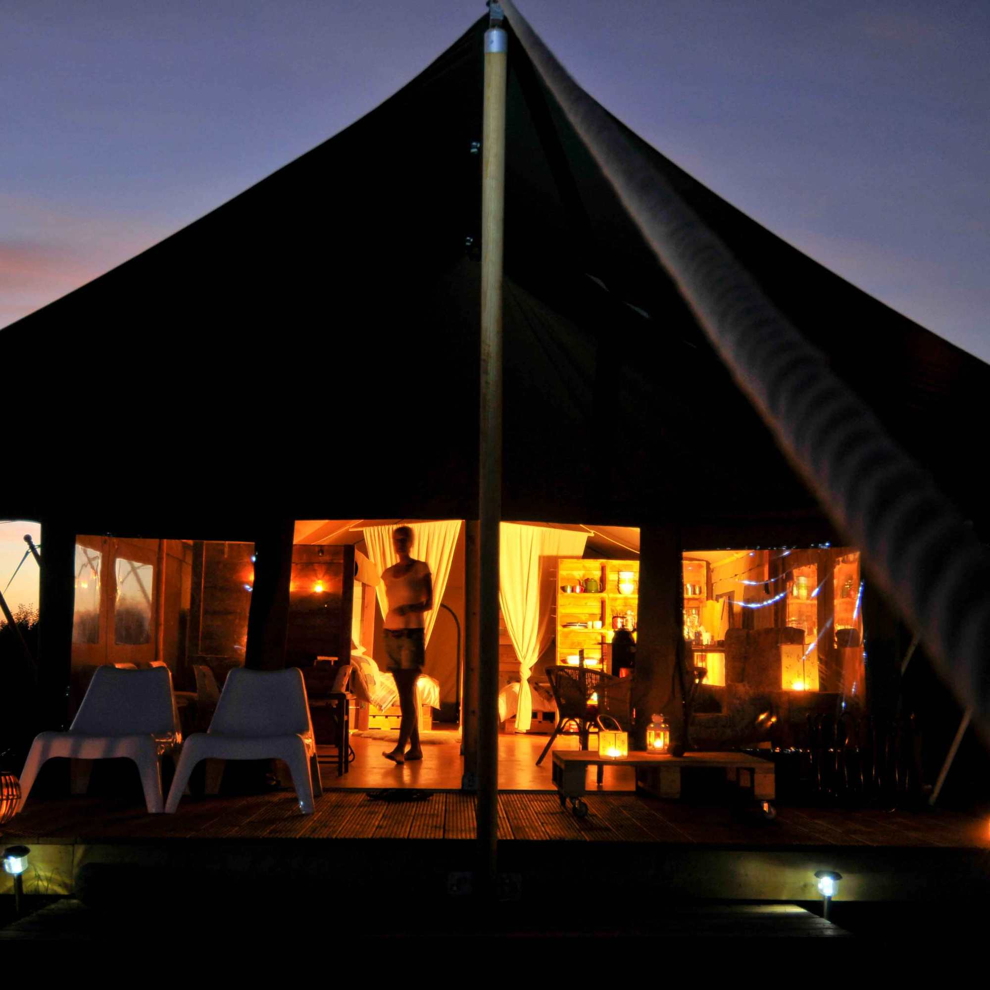 a safari tent at night with lanterns and sunset glow