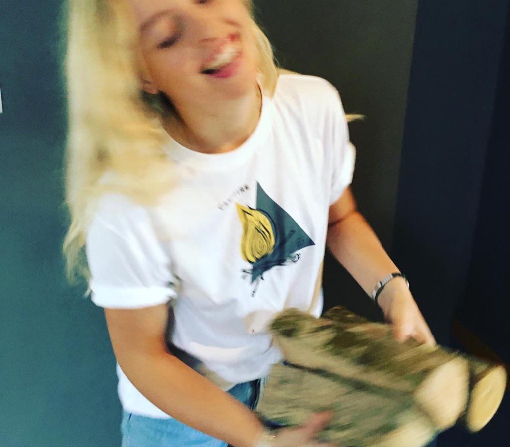girl wearing white campfire t-shirt holding logs