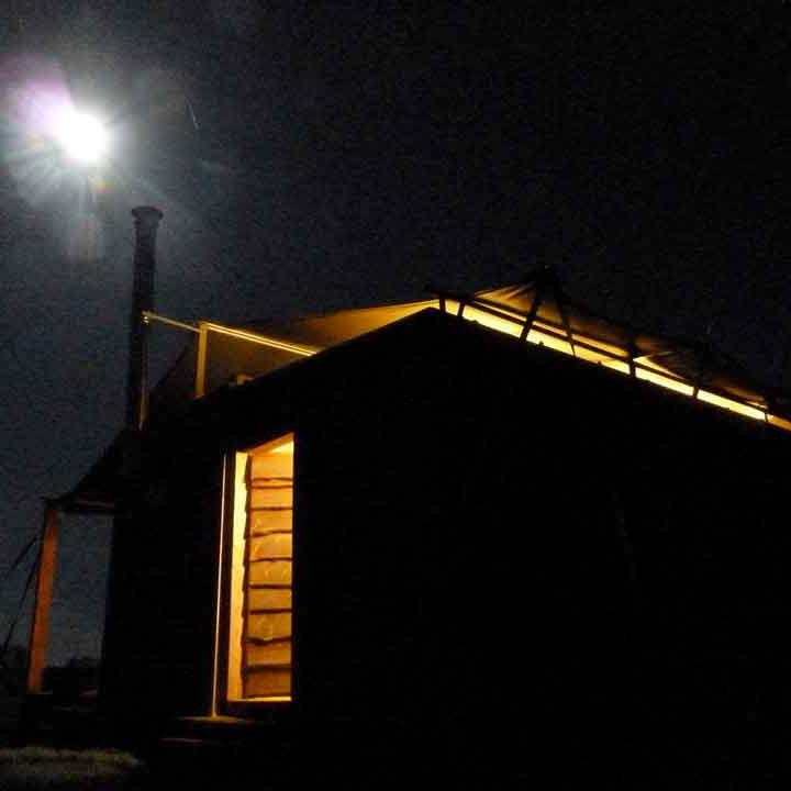 outside rusty the tin tent in the moonlight and cosy glow