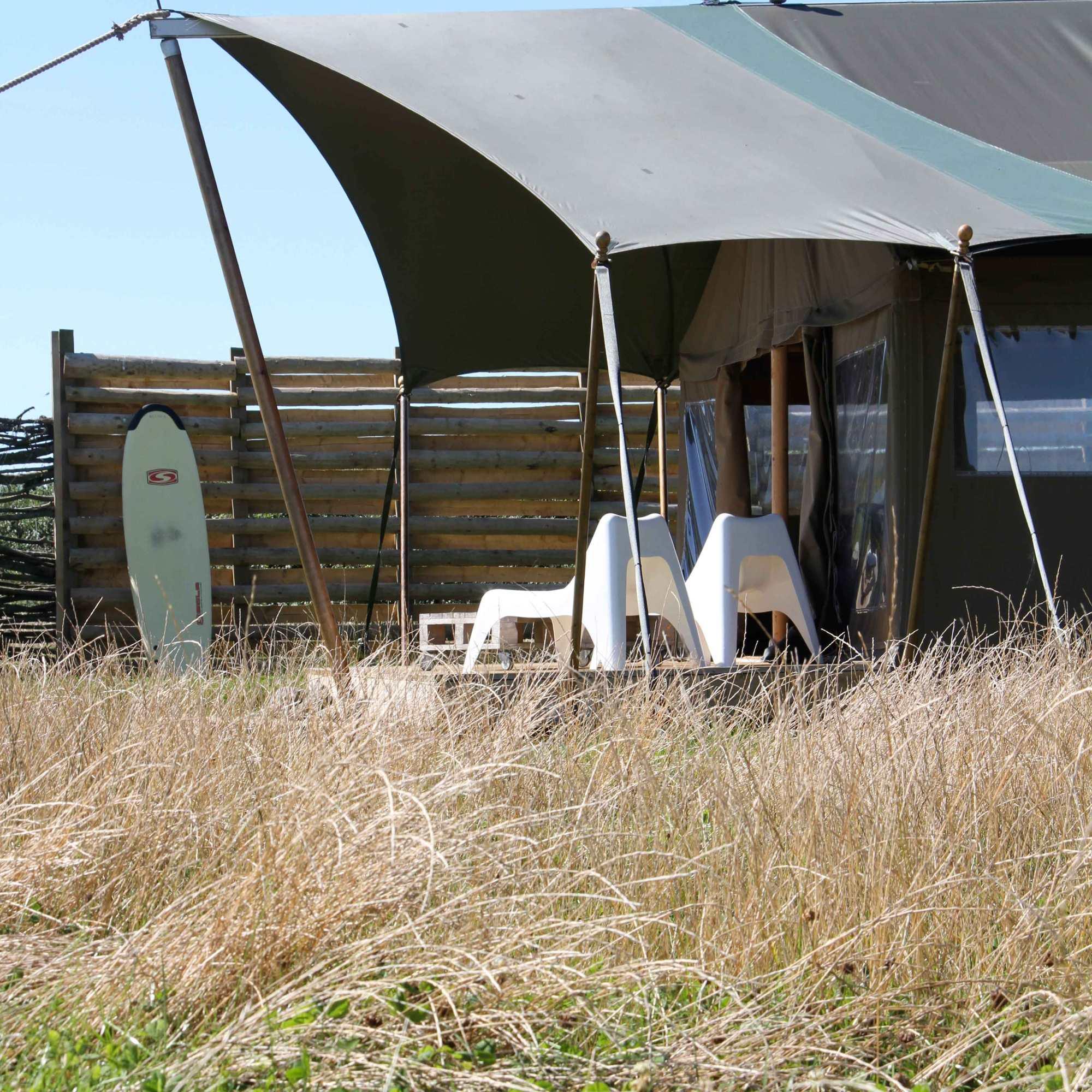 a surfboard leaning against the wooden windbreak outside Hobie safari tent