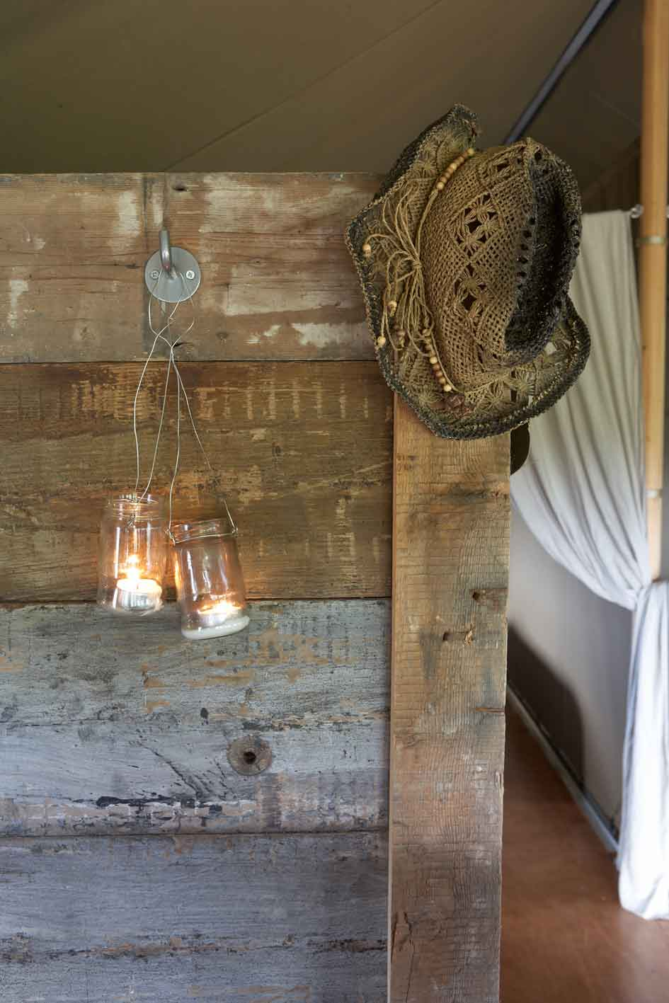 jam jar lanterns and hat hanging on the hooks on the day bed