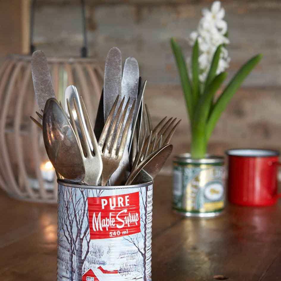 a tin of vintage cutlary with a lantern, crocus pot and enamel mug on the table